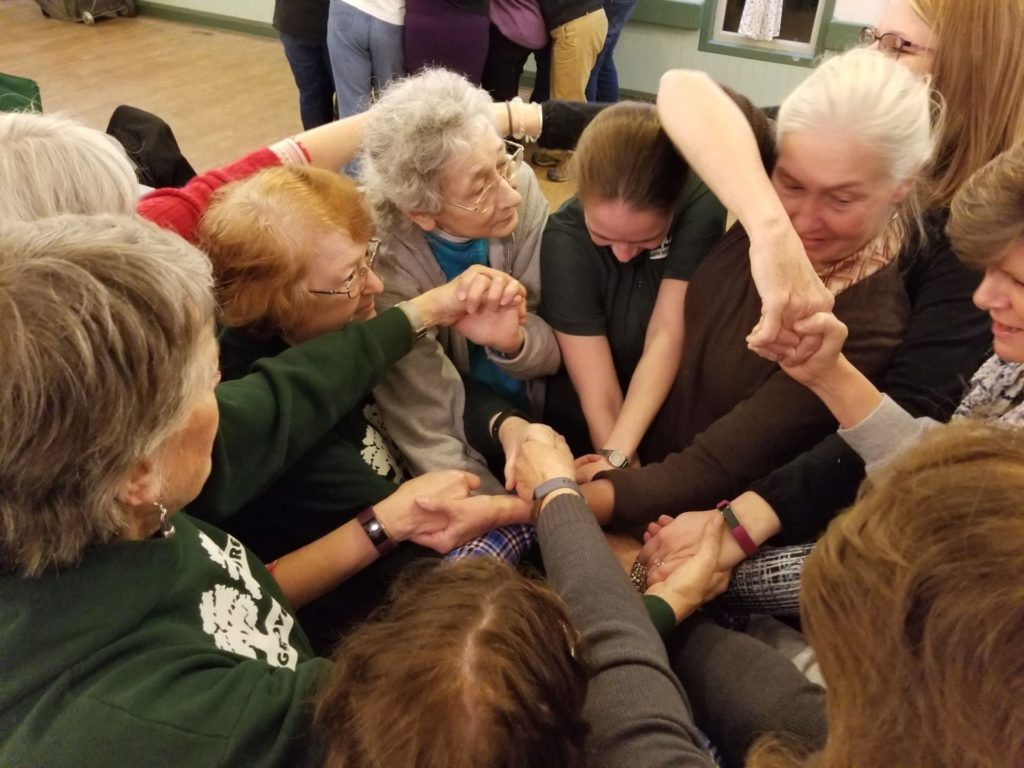 adults attempt to unravel a human knot