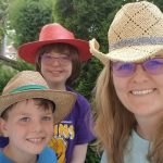 a volunteer and two campers wear big stetson-style hats and smile at the camera