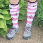 White and pink striped knee socks in front of bushes