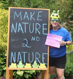 "Bean stands before a ""Make Nature 2nd Nature"" chalkboard with a paper reading ""Pepper makes you sneeze"""