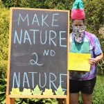 "Bean holds sign reading ""A Humdinger"" and stands by chalkboard reading ""Make Nature Second Nature"""