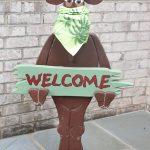 moose wears bandana and holds welcome sign
