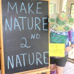 "Bean stands in front of a chalkboard reading ""Make Nature Second Nature"" and holds a sign reading ""in a hootel"""