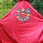 red cape pulled up over face and held open to display superman/chain breaking logo